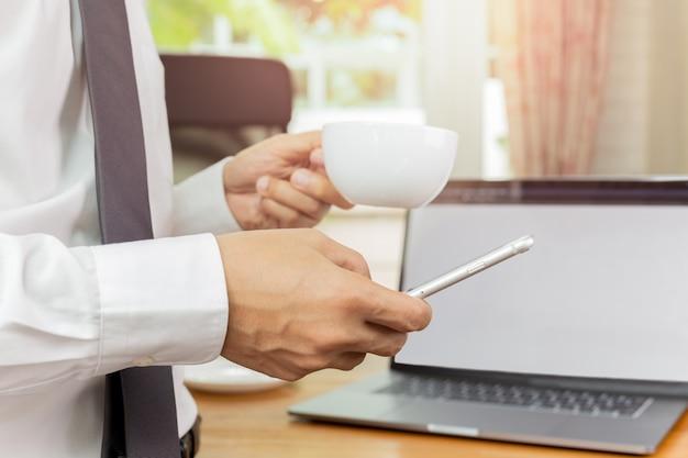 Businessmans-hand, die mobiltelefon und tasse kaffee in seinem büro hält Premium Fotos