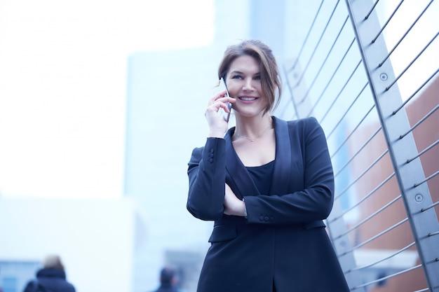 Businesswoma, das mit mobile in der städtischen umwelt spricht Premium Fotos