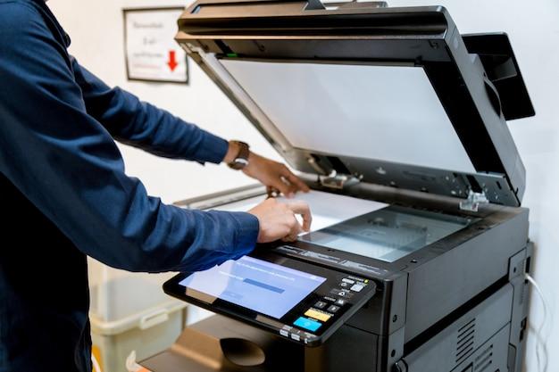 Bussiness man handpresseknopf auf platte des druckers, druckerscannerlaser-bürokopie-maschinenversorgungen beginnen konzept. Premium Fotos