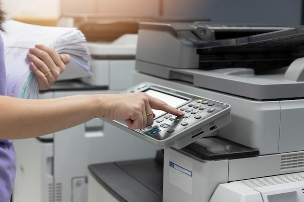 Bussinesswoman, das kopierer verwendet, um haufen der schreibarbeit im büro zu kopieren. Premium Fotos