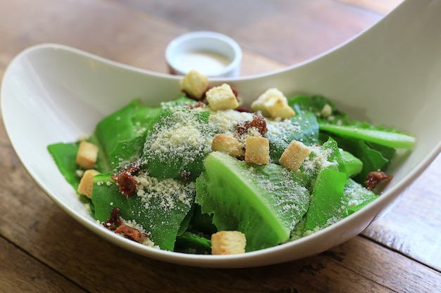Caesar salad gesunde mittagsschüssel. mit soße in tassen auf holztisch hintergrund. Premium Fotos