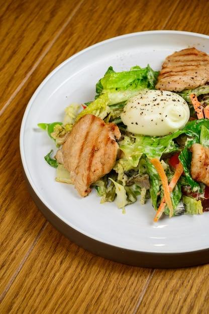Caesar salat mit croutons, wachteleiern, kirschtomaten und gegrilltem hähnchen in holztisch. köstlicher salat mit hähnchen, nüssen, ei und gemüse. Premium Fotos