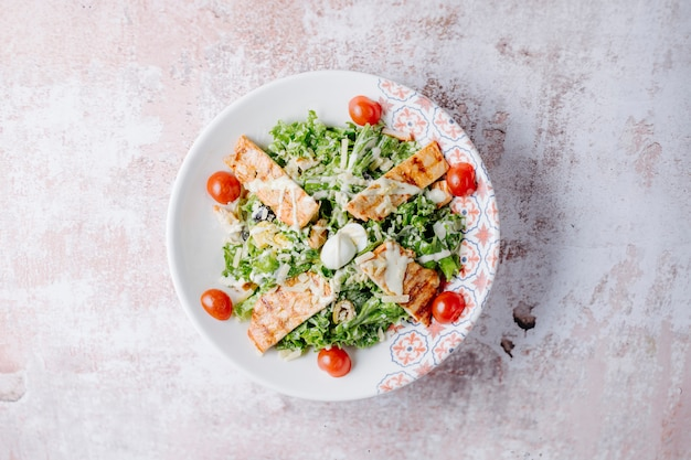 Caesar salat mit gegrillter hähnchenbrust, parmesan und kirschtomaten. Kostenlose Fotos