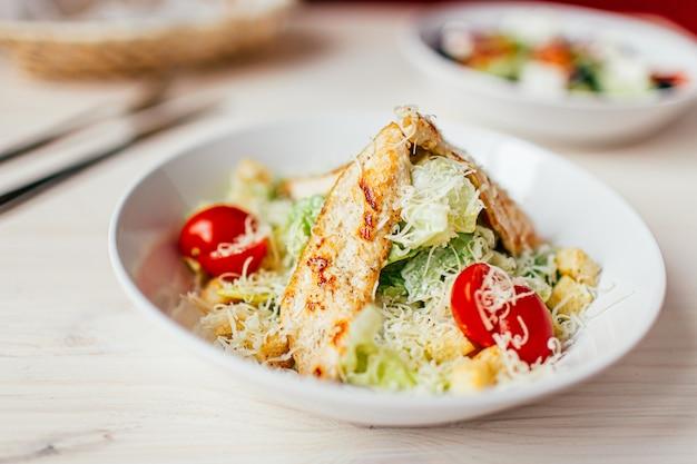 Caesar-salat mit huhn auf weißem holztisch mit gabel und messer. Premium Fotos