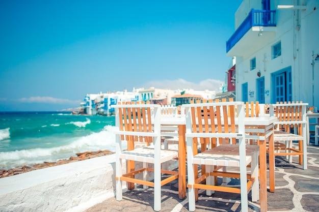 Café im freien auf einer straße des typischen griechischen traditionellen dorfs in griechenland. Premium Fotos