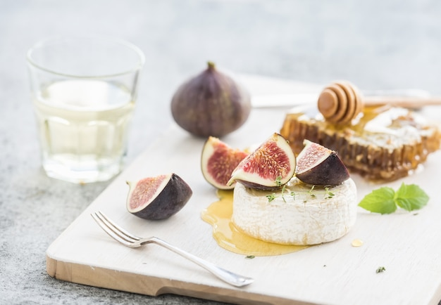 Camembert- oder briekäse mit frischen feigen, bienenwabe und glas weißwein auf umhüllungsbrett über rustikalem grauem hintergrund des schmutzes Premium Fotos