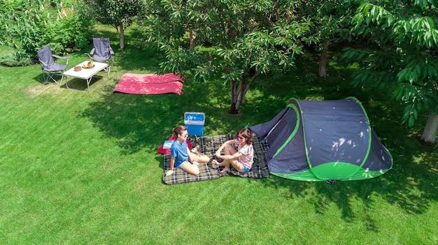 Camping-luftbild von oben mutter und tochter, die spaßzelt und campingausrüstung unter baumfamilienurlaub im lager im freienkonzept haben Premium Fotos