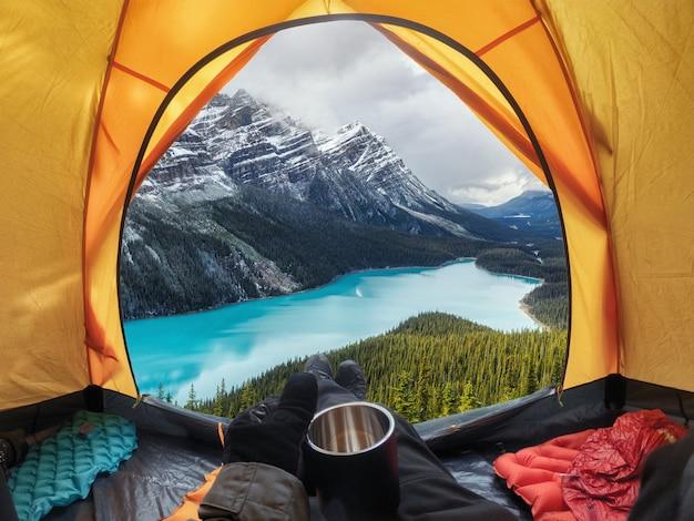 Camping mit haltebecher im gelben zelt offen mit peyto lake im icefields parkway Premium Fotos