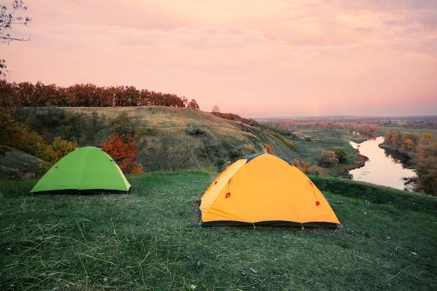 Camping von orange und grünen zelten am ufer des flusses Premium Fotos