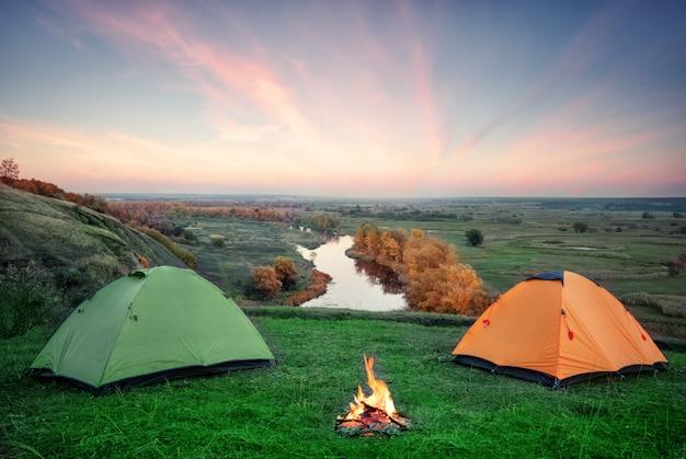 Camping von orange und grünen zelten mit feuer am ufer des flusses Premium Fotos