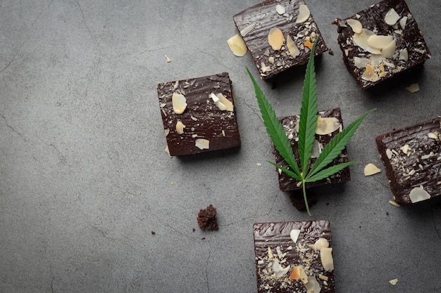 Cannabis brownies und cannabisblätter auf dunklen boden legen Kostenlose Fotos