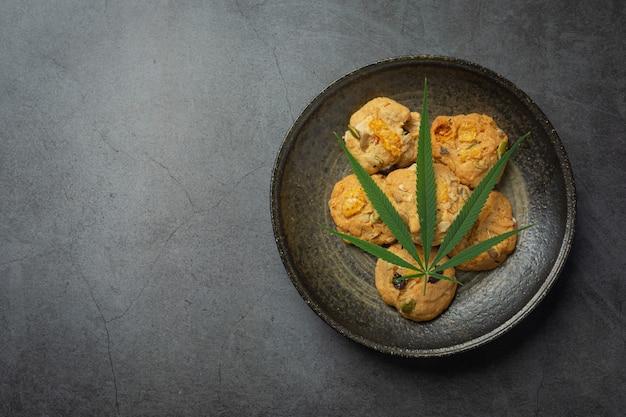 Cannabisplätzchen und cannabisblatt auf schwarzen teller gelegt Kostenlose Fotos