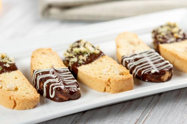 Cantuccini-kekse. italienisches biscottiplätzchen auf weißer platte auf einem weißen hölzernen hintergrund. ansicht von oben Premium Fotos