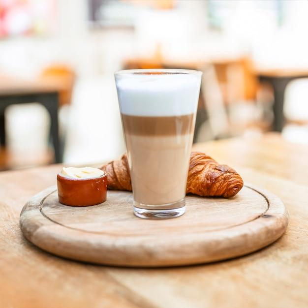 Cappuccino-kaffeeglas mit hörnchen auf hölzernem behälter Kostenlose Fotos