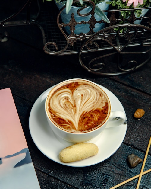 Cappuccino mit plätzchen auf dem tisch Kostenlose Fotos