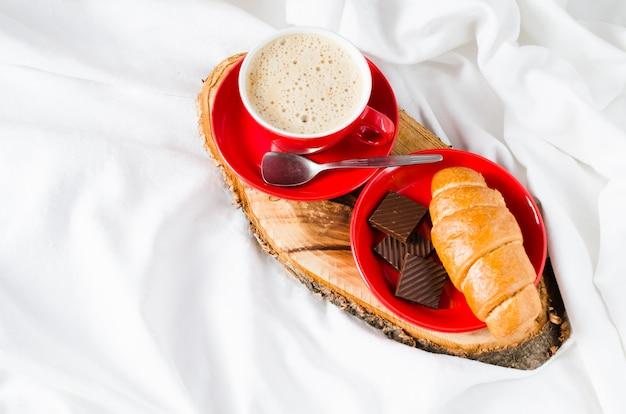 Cappuccino, schokolade und hörnchen auf einem bett. Premium Fotos