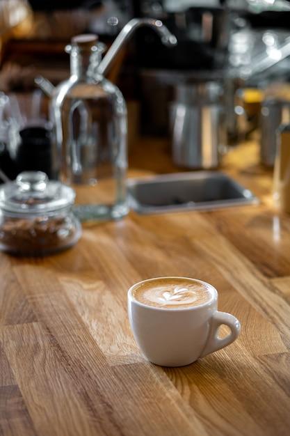 Cappuccinokaffee mit herzzeichnung am weinlesecafé. Premium Fotos