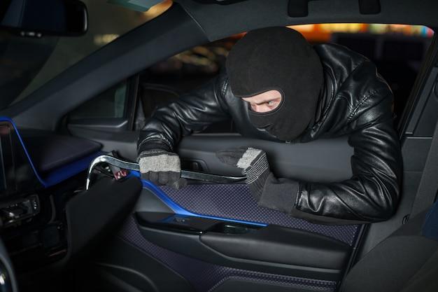 Carjacker entsperren handschuhfach mit brechstange. männlicher dieb mit sturmhaube auf seinem kopf hackt auto. carjacking-gefahrenkonzept. autotransportkriminalität Premium Fotos