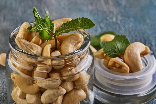 Cashew in einem durchsichtigen glas mit minzblättern darauf Premium Fotos