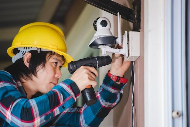 Cctv-installation mit jungen asiatischen technikern. installation wie wifi ip-kamera konzept: wireless ip-kamera Premium Fotos
