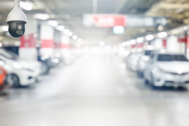 Cctv-überwachungskamera auf unschärfentiefgaragenparkplatz mit licht auf ausgangsweg Premium Fotos