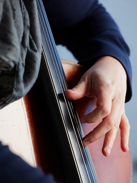Cellist spieler hände. violoncellist, der cello auf hintergrund des feldes spielt. musikalische kunst, konzept leidenschaft in der musik. professioneller cellospieler der klassischen musik solo durchführen Kostenlose Fotos