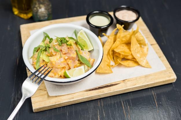 Ceviche mit soßen und pommes-frites auf einem holztisch Premium Fotos