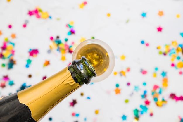 Champagne, die in glas auf leuchtpult gießt Kostenlose Fotos