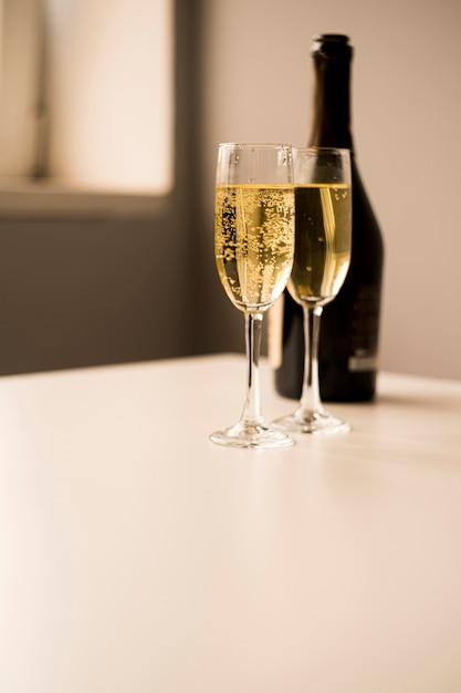 Champagne-gläser mit flasche auf weißer tabelle Kostenlose Fotos