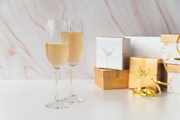 Champagne-gläser mit geschenken auf der tabelle Kostenlose Fotos