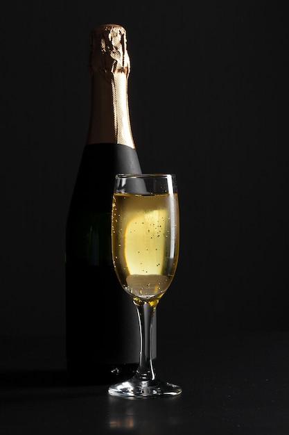 Champagne-weinglas und -flasche auf schwarzem hintergrund Premium Fotos