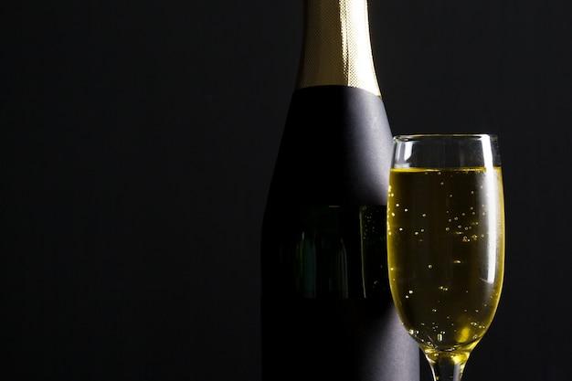 Champagne-weinglas und -flasche auf schwarzem Premium Fotos