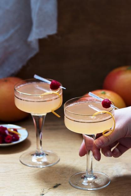Champagnercocktail mit grapefruitsaft, garniert mit eifer und himbeeren. rustikaler stil. Premium Fotos