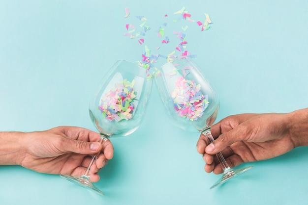 Champagnergläser prallen aufeinander und konfetti Kostenlose Fotos