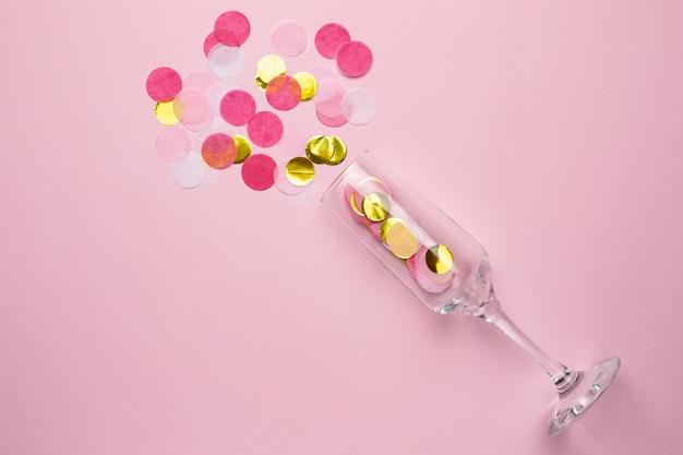 Champagnerglas mit goldenen und rosa konfetti Premium Fotos
