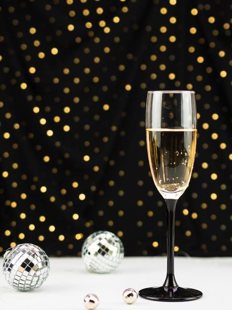 Champagnerglas mit kugeln und goldenen punkten Kostenlose Fotos