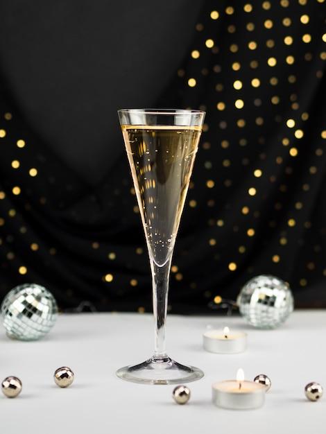 Champagnerglas mit kugeln und kerze Kostenlose Fotos