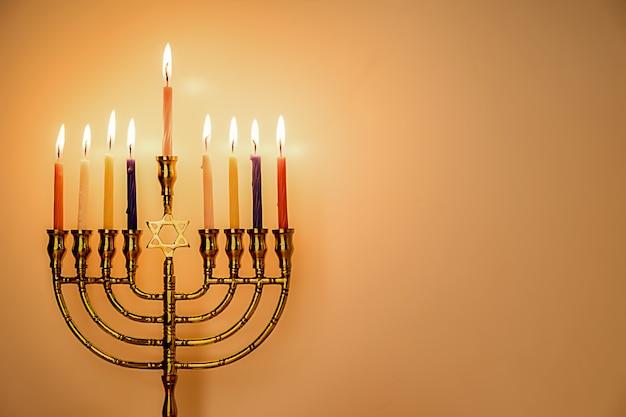 Chanukka-menorah mit brennenden farbkerzen für jüdischen feiertag mit hölzernem hintergrund. Premium Fotos