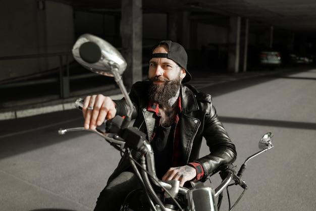 Charismatischer biker auf einem lächelnden motorrad Premium Fotos