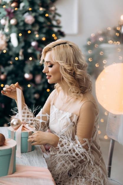 Charmante blonde frau öffnet die geschenkboxen, die vor einem weihnachtsbaum sitzen Kostenlose Fotos