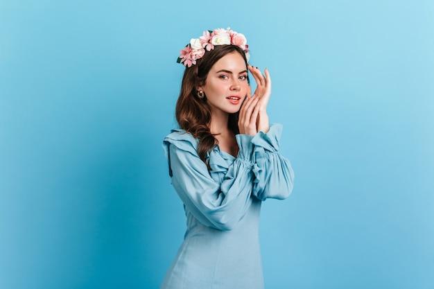 Charmante dame im eleganten blauen kleid, das auf isolierter wand aufwirft. innenporträt der jungen frau mit rosa blumen im dunklen haar. Kostenlose Fotos