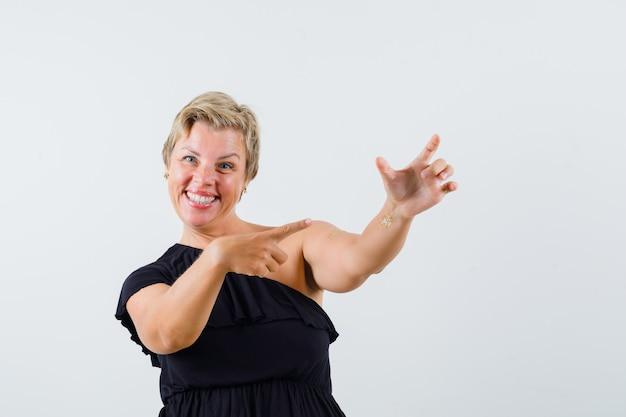 Charmante dame posiert wie auf telefon in schwarzer bluse zeigen und fröhlich aussehen. vorderansicht. Kostenlose Fotos