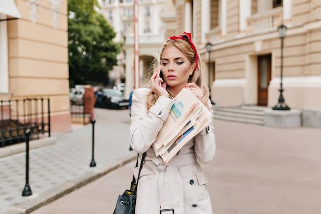 Charmante geschäftsfrau mit elegantem make-up und blonden haaren eilt zur arbeit. außenporträt der jungen frau im beige mantel, der zeitung hält und am telefon spricht. Kostenlose Fotos