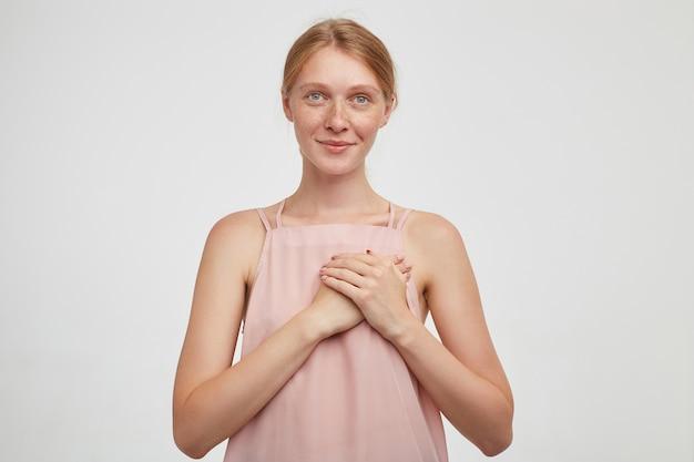 Charmante grünäugige junge rothaarige frau mit lässiger frisur, die erhobene hände auf ihrem herzen hält und kamera mit angenehmem lächeln betrachtet, lokalisiert über weißem hintergrund Kostenlose Fotos