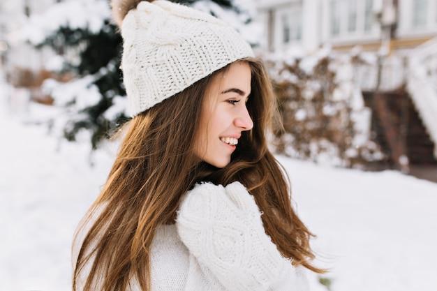 Charmante junge frau des nahaufnahmeporträts in den weißen wollhandschuhen, in der strickmütze, im langen brünetten haar, das kaltes winterwetter auf straße genießt. zur seite lächeln, echte positive emotionen, fröhliche stimmung. Kostenlose Fotos