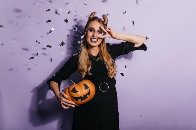 Charmante junge frau im schwarzen kleid, die halloween-karneval genießt. foto des lächelnden vampirmädchens, das orange kürbis hält. Kostenlose Fotos