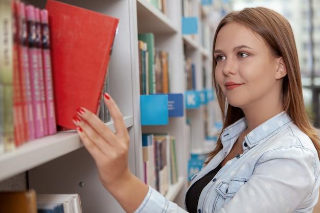 Charmante junge frau in der bibliothek oder im buchladen Premium Fotos