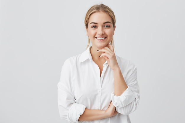 Charmante junge frau mit blonden glatten haaren, die ein weißes hemd tragen, das angenehm in die kamera schaut und ihr kinn berührt. junges hübsches mädchen mit dem zahnigen lächeln, das aufwirft. Kostenlose Fotos