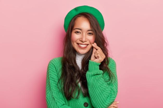 Charmante junge frau mit dunklen langen haaren macht koreanisches liebeszeichen, formt herz mit fingern, trägt hellmodische grüne baskenmütze und pullover auf knöpfen Kostenlose Fotos
