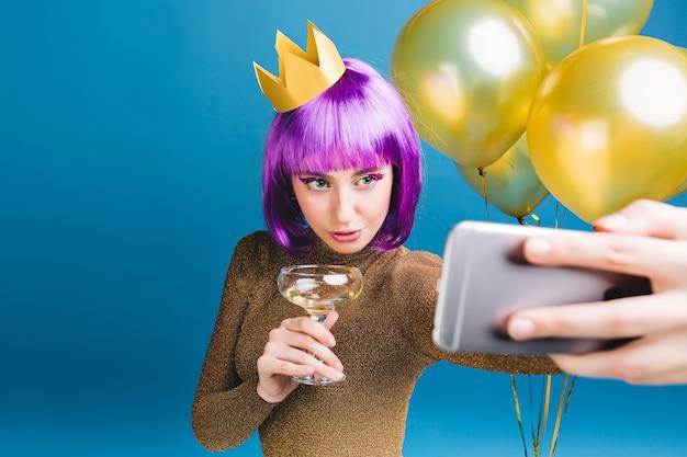Charmante junge frau mit lila haarschnitt, krone auf kopf machen selfie-porträt. goldene luftballons, champagner, neujahrsparty, luxuskleid, lametta-make-up. Kostenlose Fotos